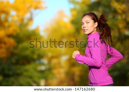 Aspirations - Aspirational woman runner running looking and thinking about future goals. Female athlete jogging in autumn forest in fall color foliage. Beautiful multiracial Asian Caucasian jogger. - stock photo