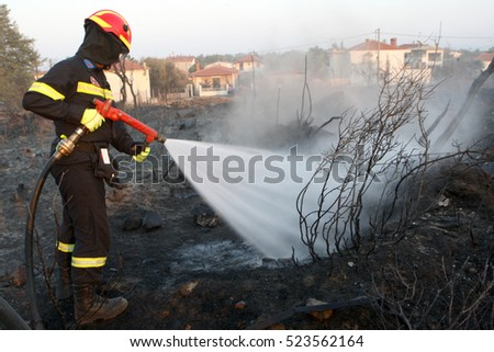 ASPROVALTA, MAKEDONIA/GREECE   AUGUST 27:  Firefighter extinguishes a fire in a field by water flooding on August 27 2012 in Asprovalta.