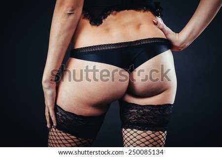 Ass of sexy woman posing in black lingerie over black background. The beautiful young sexy girl in stockings poses in studio on black background. - stock photo