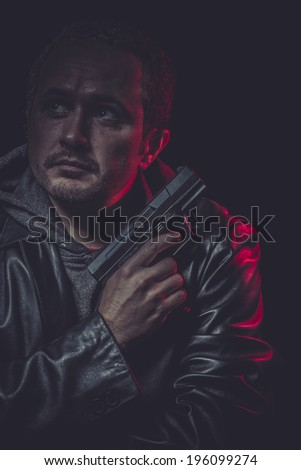 Assassin, man with black coat and gun - stock photo