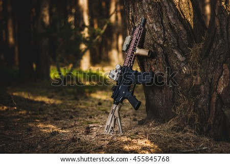 assault rifle leaning on a tree in the forest