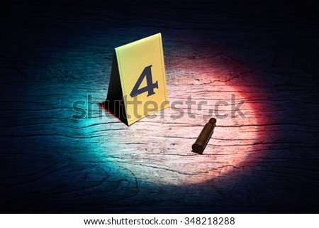 assault rifle shell marked as evidence in a spot light - stock photo