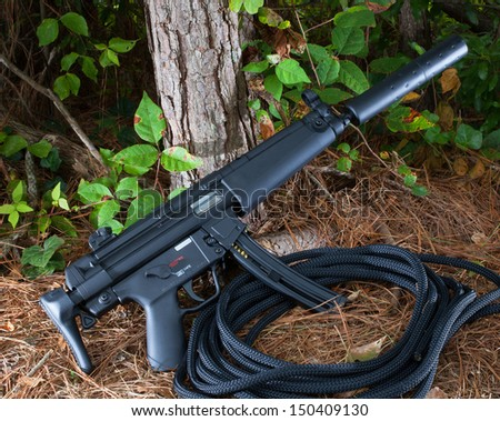 Assault rifle with a collapsible stock and suppressor - stock photo