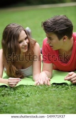 Assectionate teenage couple on a date lying holding hands on a rug in the park chatting and looking into each others eyes