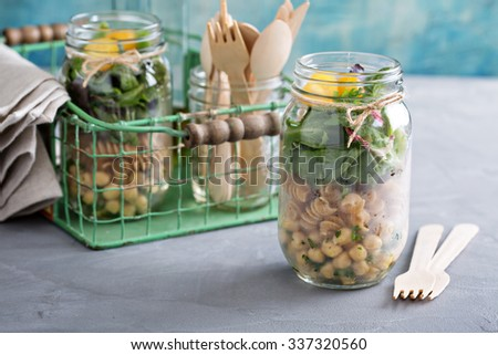 Assembling a mason jar salad for a lunch to go - stock photo