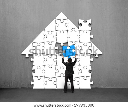 Assembling blue puzzles into house shape on concrete wall - stock photo