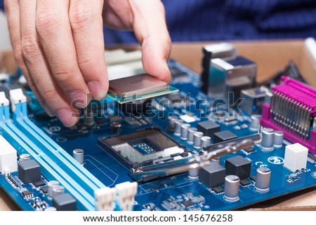 Assembling high performance personal computer, inserting CPU, processor into the motherboard socket, opened PC case in background, shallow depth of field, focus on hand - stock photo
