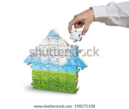 Assembling house shape puzzles in beautiful landscape in white background - stock photo
