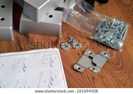Assembling parts of sofa on brown wooden floor with paper instruction - stock photo