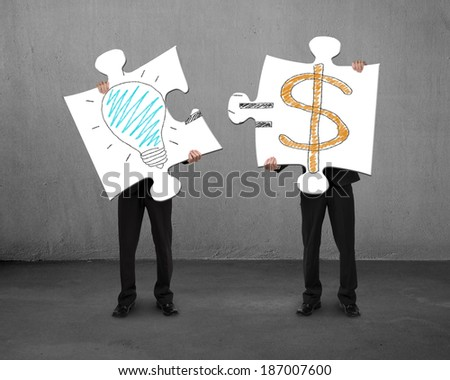 Assembling puzzles with bulb and money drawings concrete background - stock photo