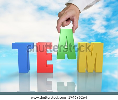 Assembling TEAM 3D word on table with blue sky reflection - stock photo