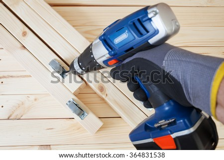 Assembling the furniture, fixing the wheels with cordless screwdriver. Close up. - stock photo