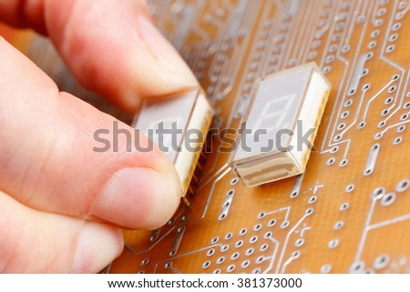 Assembly of electronic components on circuit board - stock photo