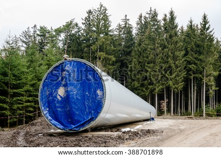 Assembly of wind turbines - the lower part of a wind turbine is waiting to be erected in a forest glade - stock photo