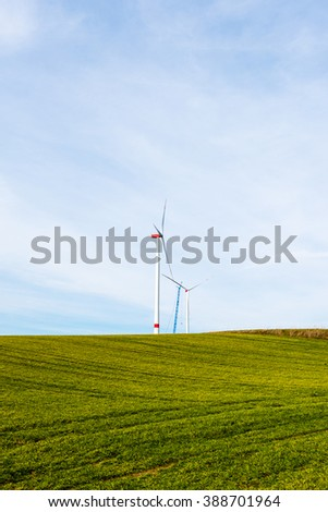 Assembly of wind turbines - two wind turbines in different stages of completion - one still with crane. Green fields in the foreground - stock photo