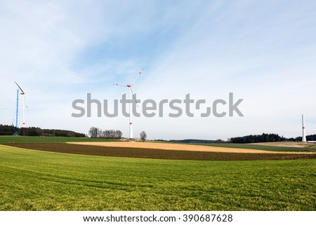 Assembly of wind turbines - 3 wind turbines in different stages of completion - one with crane. Green fields in the foreground - stock photo