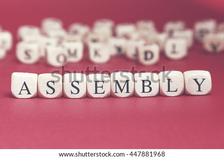 Assembly word written on wood cube with red background
