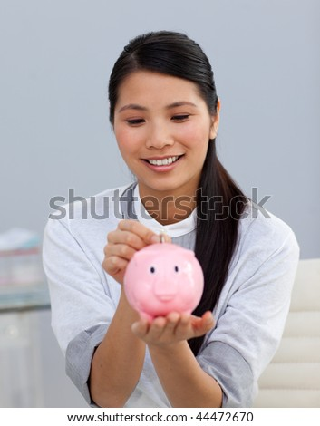 Asserive businesswoman saving money in a piggybank in the office - stock photo