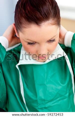 Assertive female surgeon wearing scrubs in the hospital - stock photo
