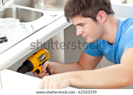 Assertive man holding a drill repairing a kitchen sink at home - stock photo