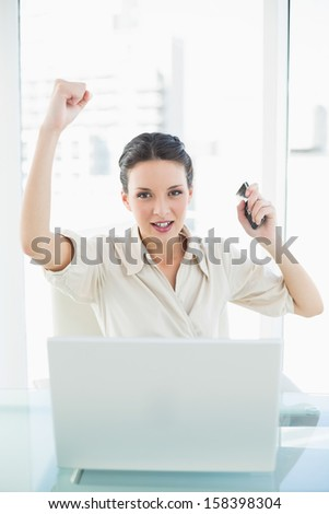 Assertive stylish brunette businesswoman raising her fist in bright office