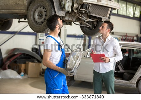 assessor and repair man talking about the damage - stock photo