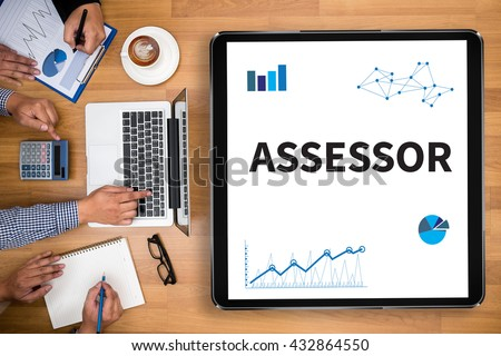 ASSESSOR Business team hands at work with financial reports and a laptop - stock photo