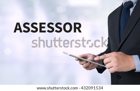 ASSESSOR Businessman use a tablet computer - stock photo