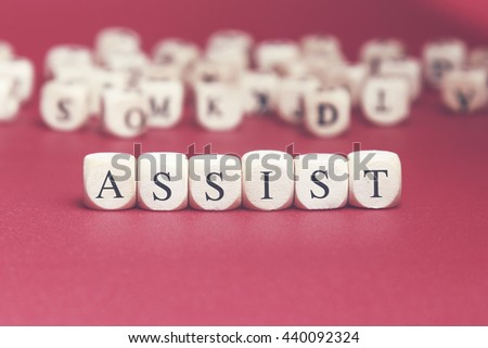 Assist word written on wood cube with red background