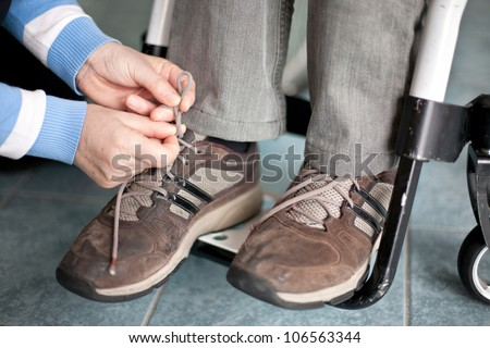 assistance for a disabled man in wheelchair, tying shoes - stock photo