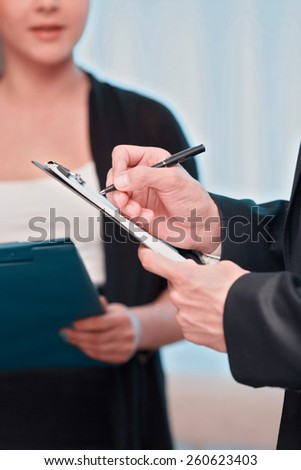 Assistant at work. Closeup of beautiful young woman in formalwear holding documents and reporting while having meeting with her boss