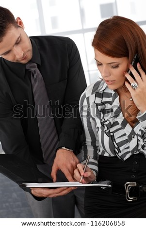 Assistant holding contract for busy elegant businesswoman to sign.
