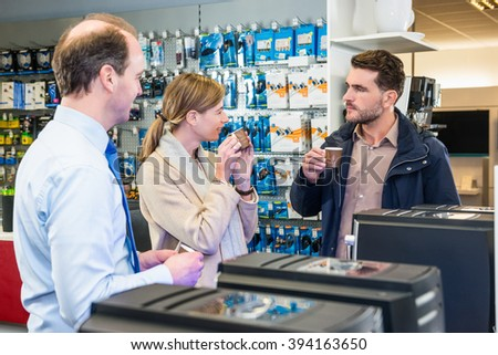 Assistant looking at couple tasting coffee before buying espresso maker in electronics store