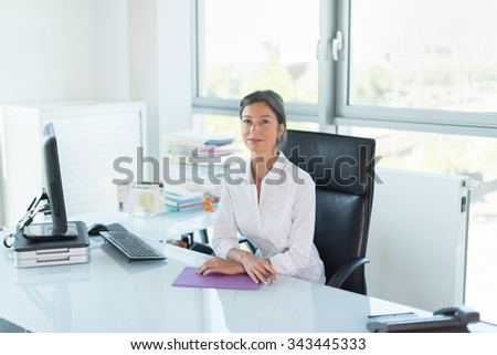 assistant manager looking at camera in her white office Woman sitting at a tidy glass desk in front of a black computer She is wearing a white shirt her hair are tied Her hands are crossed on a folder