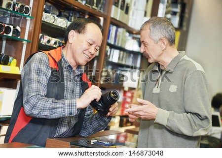 Assistant seller help buyer by demonstrating digital photo camera at shop store - stock photo