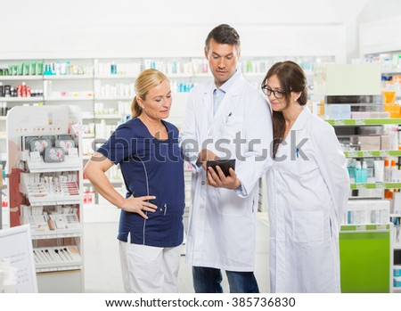 Assistant Using Digital Tablet With Pharmacists - stock photo