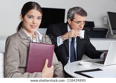 Assistent with datebook sitting near a businessman in the office - stock photo