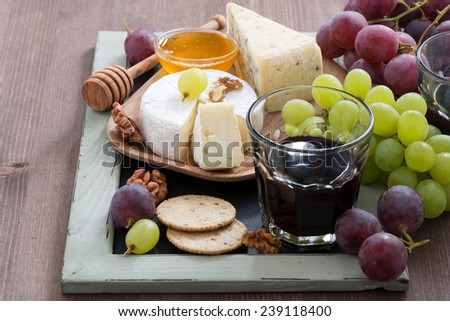 Assorted appetizers to wine - cheeses, fresh grapes, crackers and honey, horizontal - stock photo