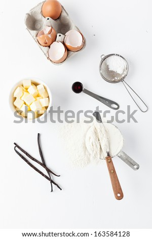 Assorted baking ingredients and tools: eggshells, vanilla pods, flour in measuring cup, spatula, measuring spoon, butter and vintage sifter with icing sugar. Taken on a white background, from above. - stock photo