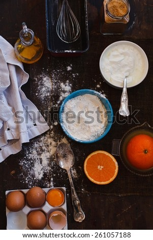 Assorted baking ingredients and tools:  flour in measuring cup, eggshels, cup of yogurt, juicer of orange, taken over dark wood table. Homemade Baked biscuit cake. Step on step.  Top view. - stock photo