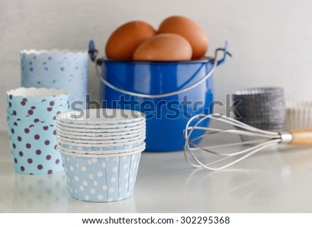 assorted baking tools: mini tart tins, eggs, hand whisk, and paper mould cake, - stock photo