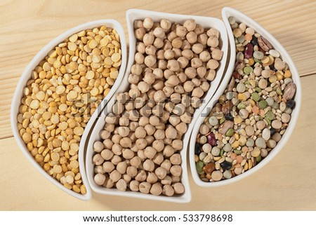Assorted beans in bowls on wood background