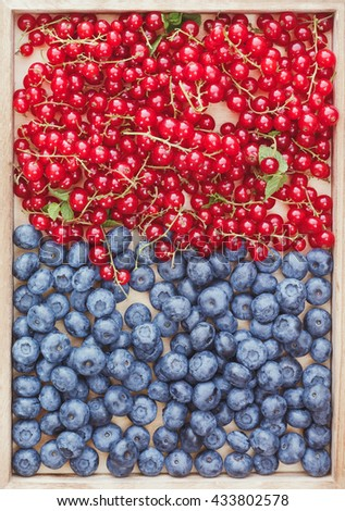 Assorted berries. Fresh redcurrants and blueberries on wooden tray, top view - stock photo