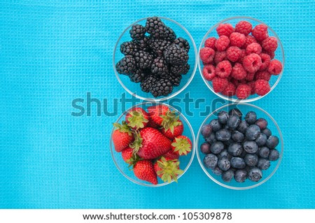 Assorted berries in bowls on blue background - stock photo