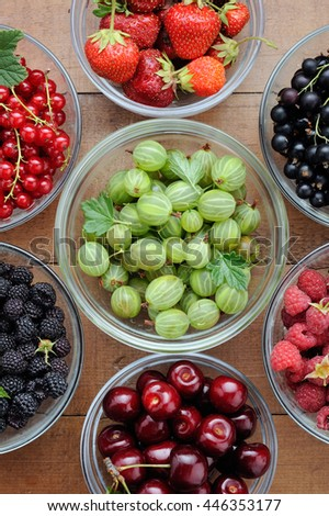 Assorted berries in glass bowls on wooden background: red and black currant, red and black raspberry, strawberry, cherry and gooseberry