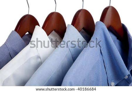 Assorted blue dress hanging on wooden hangers - stock photo