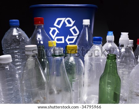 Assorted bottles and trash bin with recycle sign - stock photo