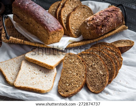 Assorted bread slices in a basket on a white linen tablecloth and wooden background