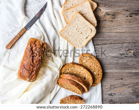 Assorted bread, slices of rye bread on linen tablecloths, grey wooden background - stock photo