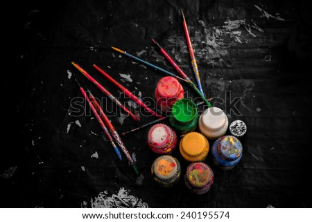 Assorted brushes and colors of artist palette over black cloth. - stock photo